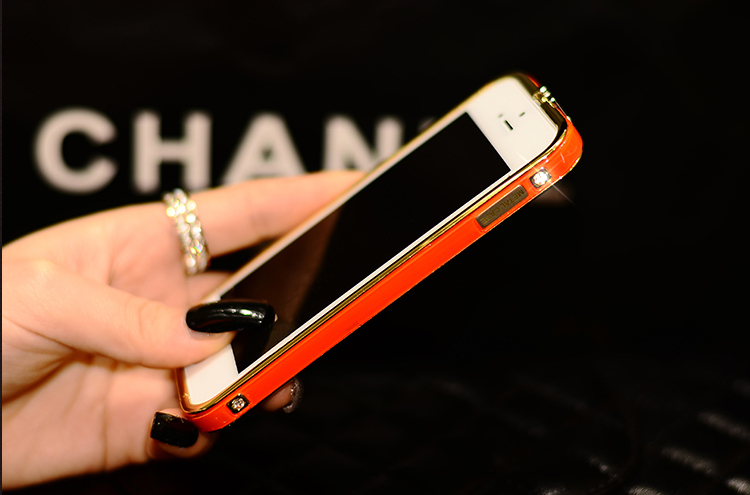 Чехол-каркас для iPhone 5, 5S, 6 разных цветов со стразами и золотой обводкой в руках красного цвета
